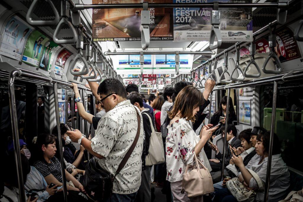 電車でスマホをいじる人々