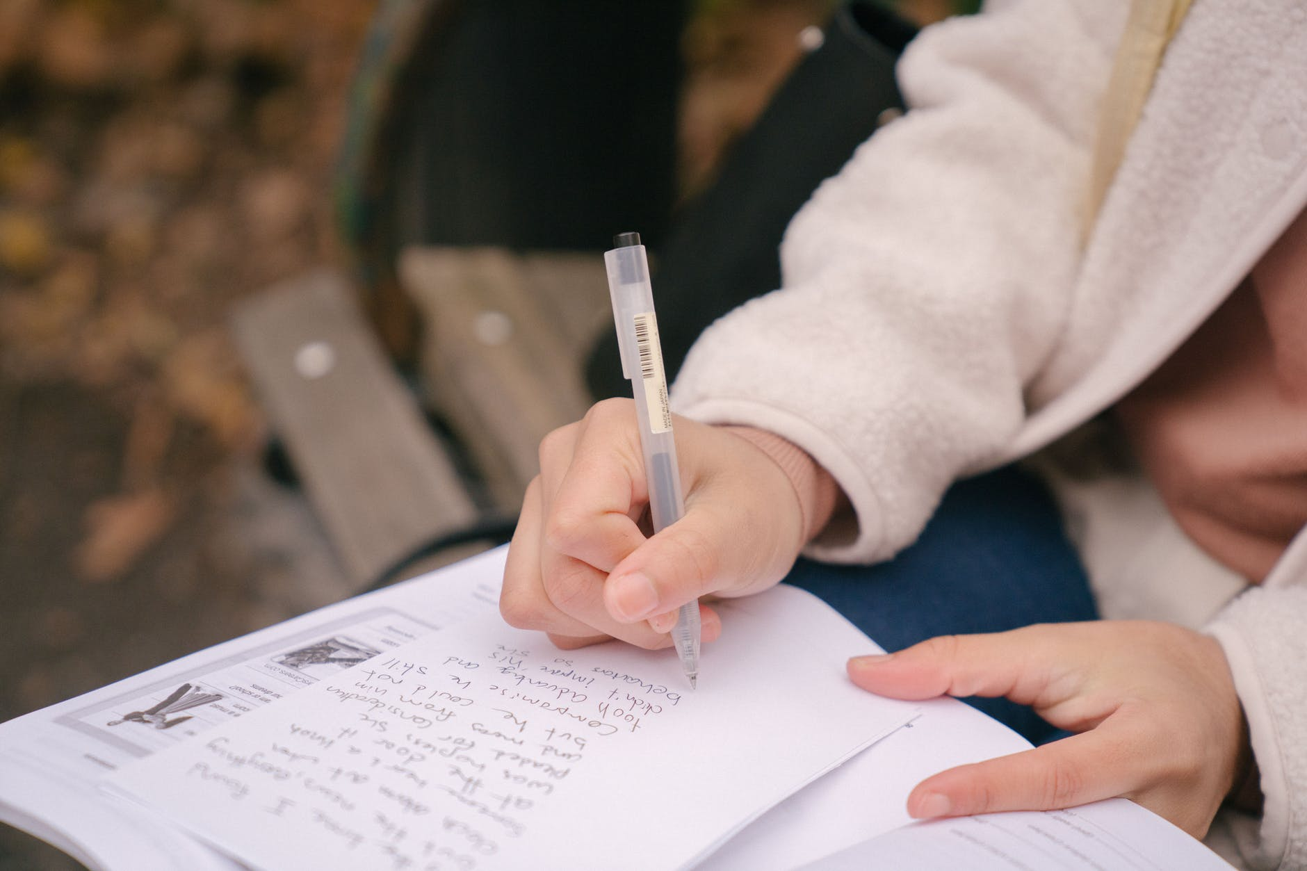 anonymous female writing information on paper with textbook on bench